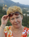 Mature woman straightens sunglasses. Portrait of an attractive mature woman straightens sunglasses, against a background of mountain scenery Stock Photo