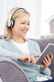 Mature Woman Streams Music From Digital Tablet To Wireless Headp Stock Images