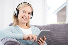 Mature Woman Streams Music From Digital Tablet To Wireless Headp Royalty Free Stock Images
