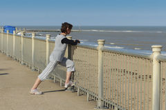 Mature woman streching by the beach Stock Images