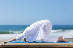 Mature woman stretching beach Stock Images
