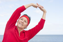Mature woman stretching exercise ocean Stock Photos