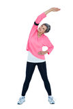 Mature woman stretching while listening music Stock Photography