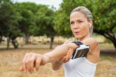 Mature woman stretching at park royalty free stock image
