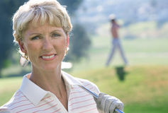 Mature woman in striped polo shirt and golf glove standing on golf course, holding putter on shoulder, smiling, close-up, portrait Stock Image