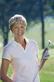 Mature woman in striped polo shirt and golf glove standing on golf course, holding putter, smiling, portrait Stock Photo