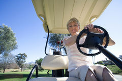 Mature woman, in striped polo shirt, sitting in golf buggy on golf course, smiling, front view, portrait, low angle view Royalty Free Stock Images