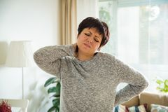 Mature woman suffering from backache. At home. Massaging neck with hand, feeling exhausted, standing in living room Royalty Free Stock Photo