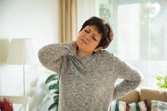 Mature woman suffering from backache. At home. Massaging neck with hand, feeling exhausted, standing in living room Royalty Free Stock Image