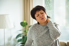 Mature woman suffering from backache. At home. Massaging neck with hand, feeling exhausted, standing in living room Stock Photos