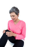 Mature woman suffering from knee pain. Over white bckground royalty free stock image