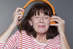 Mature woman suffering from listening to loud music on headphone Royalty Free Stock Photography