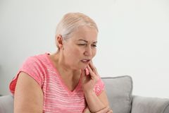 Mature woman suffering from strong tooth pain at home. Space for text stock photo