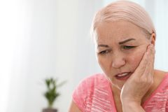 Mature woman suffering from strong tooth pain at home. Space for text royalty free stock images