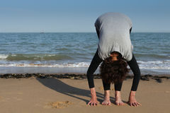 Mature woman sun salutation yoga on the beach royalty free stock images