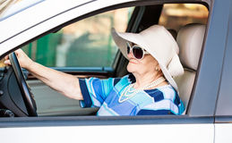 Mature woman in sunglasses driving automobile Stock Images