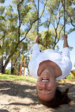 Mature woman swinging on playground upside down. An attractive mature woman in her fifties is having fun at a playground while hanging upside down in a swing Royalty Free Stock Photography