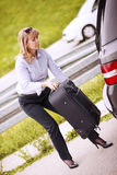 Mature woman take suitcase from car. Woman pulling out a baggage of her car trunk Royalty Free Stock Photos