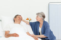 Mature woman taking care of her husband Stock Image