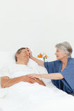 Mature woman taking care of her husband Stock Images