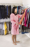 Mature woman taking clothes off closet racks Stock Photography