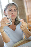 Mature woman taking drugs. Senior woman reading medication instructions on internet Royalty Free Stock Photo