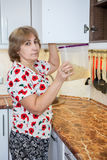 Mature woman taking glass volume with dry pasta on the shelve of food cupboard on the kitchen Stock Images