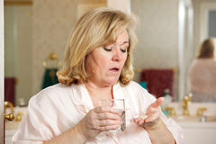 Mature woman taking medicine Royalty Free Stock Image