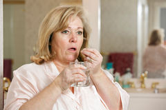 Mature woman taking medicine Royalty Free Stock Images