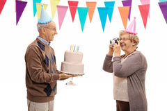 Mature woman taking picture of elderly man celebrating his birth. Mature women taking a picture of an elderly men with a cake celebrating his birthday isolated Stock Images