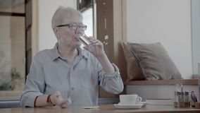 Mature woman taking pills. Energetic woman drinks some water pills. stock video