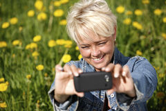 Mature woman taking selfie. Royalty Free Stock Images
