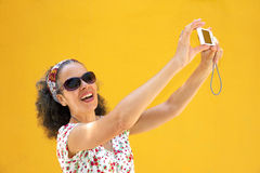 Mature woman 50s taking selfie Yellow background. A mature woman in her 50s is taking a photo of herself with a digital point-and-shoot camera. A yellow wall is royalty free stock images
