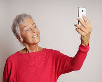 Mature woman taking a selfie with smartphone. Happy smiling mature woman in her sixties taking a selfie or self portrait with her smartphone Royalty Free Stock Photo