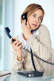 Mature woman talking on both telephone Stock Photos