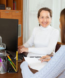 Mature woman talking with employee Stock Images
