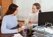 Mature woman talking with employee Stock Image