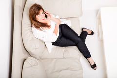 A mature woman talking on her cell phone on the sofa Royalty Free Stock Image