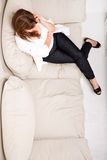A mature woman talking on her cell phone on the sofa Stock Photos