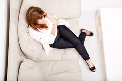 A mature woman talking on her cell phone on the sofa Stock Photo