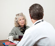 Mature Woman Talking with Her Doctor Royalty Free Stock Images