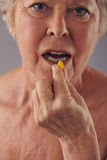 Mature woman talking medicine pill Royalty Free Stock Photography