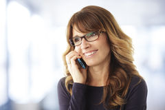 Mature woman talking on phone Stock Images