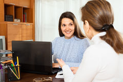 Mature woman talking with young female employee. Mature women talking with young female employee with laptop at office royalty free stock photography