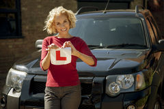 A mature woman tearing up a learner driver plate Royalty Free Stock Photography
