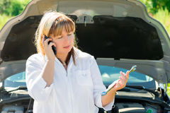 Mature woman with a telephone and a wrench Stock Photos