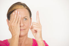 Mature woman testing focus of eyesight Stock Photo
