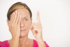 Mature woman testing focus of eyesight Stock Photo