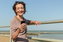 Mature Woman texting from the beach Royalty Free Stock Photography