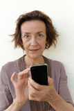 Mature woman texting. Mature woman with smartphone, checking her social media or texting while looking at camera Royalty Free Stock Photo